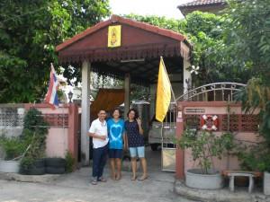 Khan, Kai, Namwaan vor ihrem Haus. Links: Thai-Fahne, rechts Königs-Fahne
